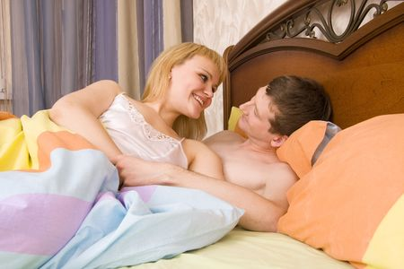 Portrait of a happy couple lying on bed. Young attractive happy amorous woman and man at bedroom. Loving couple have fun photo