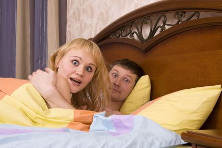 Young attractive happy amorous couple at bedroom. Woman and man are lying on bed. Loving female and male playing in the bed. Ñouple have over the barrel photo
