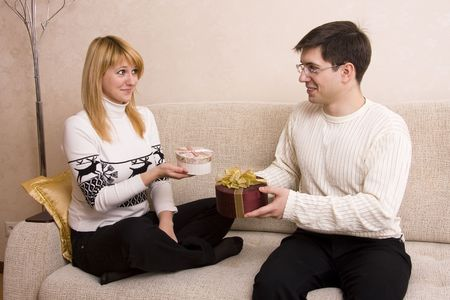 congratulate: Happy couple. Man is giving gifts woman at Valentine�s day. Female congratulate  male at Christmas.