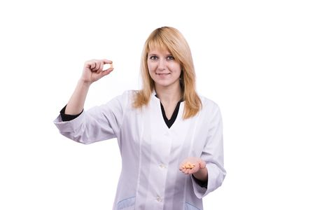 A nurse holds a small orange pill in her fingers. Female pharmacist is holding tablets. Woman  health care professional with a prescription. 