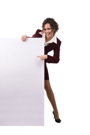 Whole-length portrait of businesswoman holding white blank card against isolated white background. A beautiful young business woman is holding a blank white sign. Business female standing beside a billboard