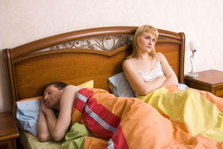 sleeplessness: Giovane coppia in una donna alesato letto. Uomo e donna, avendo un disaccordo. Maschio � addormentato e femmina con espressioni triste.  Archivio Fotografico