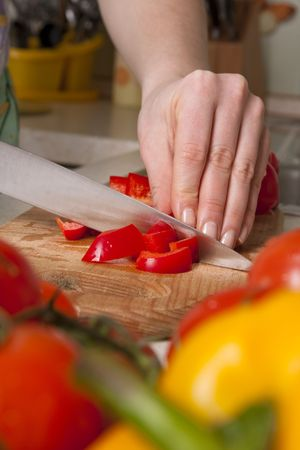Woman working in the kitchen chopping up the vegetables. Female slicing pepper for salad. Close up chef cutting vegetables.