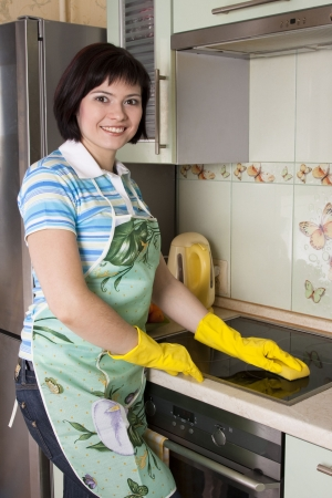 Young woman cleaning  cooker at the kitchen. Smiling female washing stove top.
