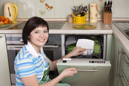 Female using dishwashing machine. Attractive brunette woman cleaning kitchen. Stock Photo