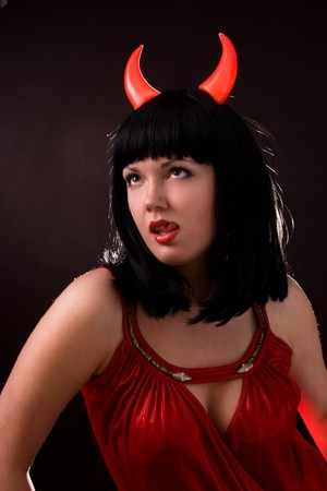 Sexy Halloween devil girl witch on dark background. Beautiful woman with Devil horns. Portrait of young woman dressed as pretty devil.Sexual Young Woman in a Costume of Red Female Devil Stock Photo - 7169664