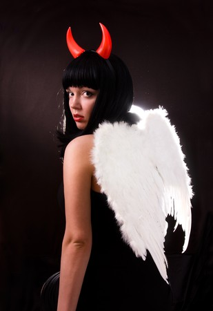Woman is an angel and  devil. Sexy Halloween devil girl witch on dark background. Beautiful woman with Devil horns. Portrait of young woman dressed as pretty angel.