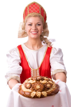 Bread-and-salt welcome. A traditional ritual of offering bread and salt to a welcome guest. Girl standing in Russian traditional costume. Woman is wearing sarafan and kokoshnik.  Standard-Bild