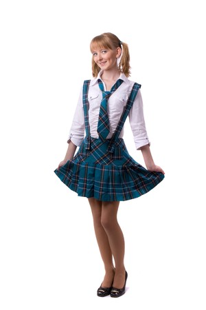 A young and beautiful schoolgirl  is wearing a traditional uniform is smiling on white background. Senior high school student in uniform is posing