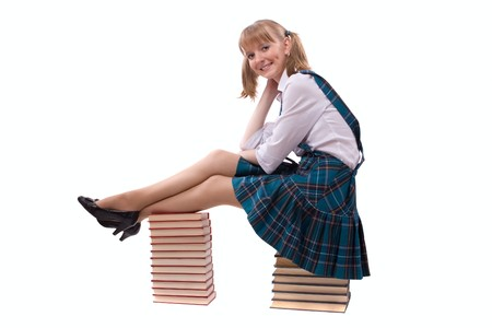 plisse: Senior high school student in uniform with documents is sitting on the stack of book. A young and beautiful schoolgirl  is wearing a traditional uniform with textbooks.