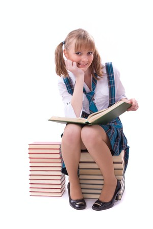 pleated: Senior high school student in uniform with documents is sitting on the stack of book. Young and beautiful schoolgirl  is wearing a traditional uniform is reading textbook.