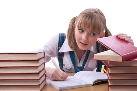 Girl studying hard for exams. Young and beautiful schoolgirl  is wearing a traditional uniform watch furtively at the textbook.