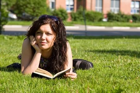 actividades recreativas: Estudiante de secundaria, mentir en la hierba en el campus de la escuela leyendo un libro. Estudiante estudiando sobre el c�sped. Libro de lectura de la joven y bella mujer en Parque