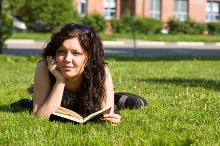 school campus: High school student, lying in grass on school campus reading a book. Student studying on the grass. Beautiful young woman reading book at park