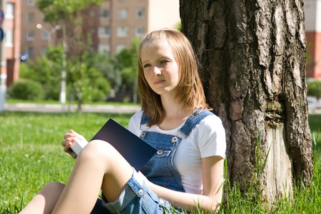 High school student, lying in grass on school campus reading a book. Student studying on the grass. Beautiful young woman reading book at park Stock Photo - 7169784