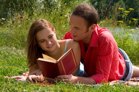 Young cople laying on a blanket on the grass on a hot summer day and reading book.  Woman and man are enjoying the sunshine in a park. Just happy couple relaxing. photo