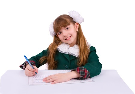 Portrait of a sweet little girl at her classroom, writing an exam. A happy schoolgirl doing her homework. Young student writing. photo