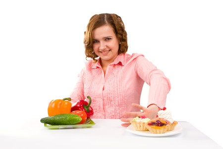 Woman makes choice between cakes and healthy vegetables on white background.  To eat or not to eat