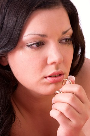 Very sad woman suffers and struggles because of infidelity. Girl feeling sad, depressed, grief. Distraught woman is very upset and holding gold wedding ring. photo