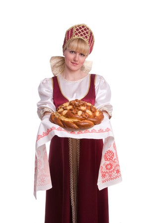 russian ethnicity: Bread-and-salt welcome. A traditional ritual of offering bread and salt to a welcome guest. Girl standing in Russian traditional costume. Woman is wearing sarafan and kokoshnik.   Stock Photo