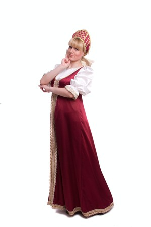 Girl standing in Russian traditional costume. Woman is wearing sarafan and kokoshnik . The girl in red old russian dress. Isolated on white. Foto de archivo
