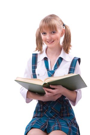 Senior high school student in uniform with documents is sitting on the stack of book. Young and beautiful schoolgirl  is wearing a traditional uniform is reading textbook. Stock Photo - 7228388