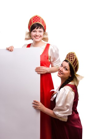 Girls standing in Russian traditional costume is smiling holding white blank card against isolated white background. Women is wearing sarafan and kokoshnik and is holding a blank white sign .  photo