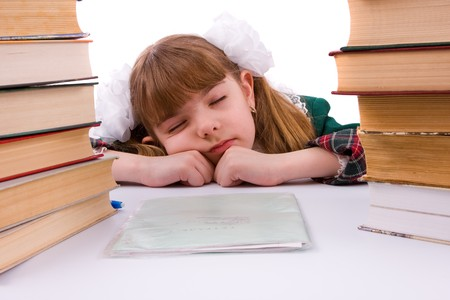 Portrait of a sweet little girl at her classroomk. Schoolgirl is sleeping near her homework. Young student is tired. photo