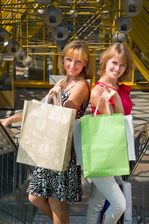 Beautiful young women shopping. Young woman holding several bags in shopping centre. Two friends on a shopping tour in the city  photo