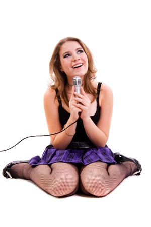 Singer. Young girl singing into microphone. Stock Photo