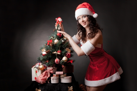 Santa girl decorates Christmas tree