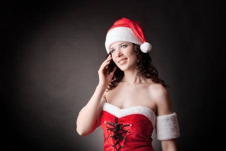 Santa girl speaks on the mobile phone
