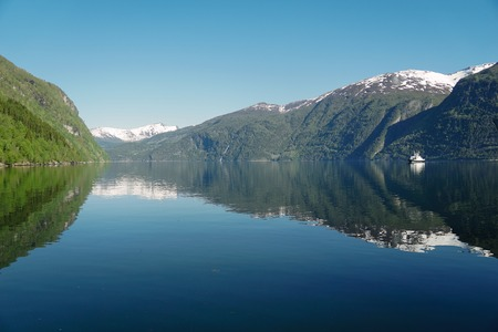 Norway beautiful spring landscape. Mountains reflection in calm water of fjord 写真素材