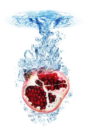 Pomegranate splashing into water against a white background.