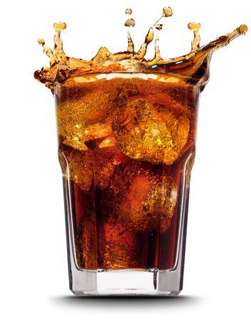 Droped cubo de hielo en el vidrio de cola y de cola salpicaduras Foto de archivo