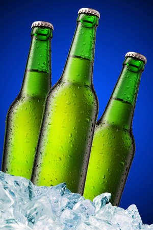 A beer bottle sitting in a container of ice on blue background photo