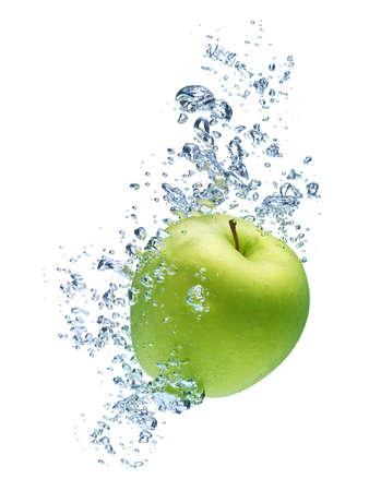 Manzana verde bajo el agua con un rastro de burbujas transparentes.