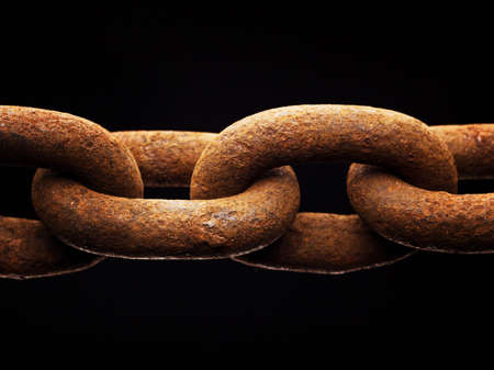Macro of rusty chain isolated on black background photo