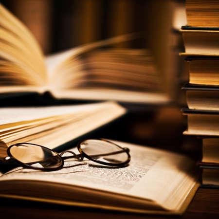 図書館: メガネを掛けて本棚の上に横たわる本を開く