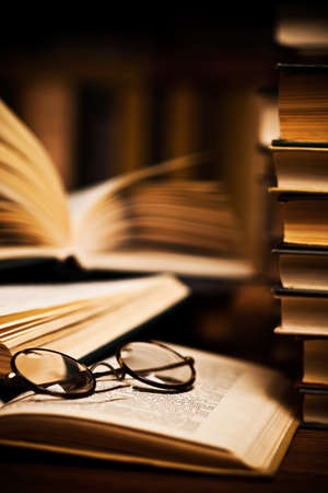 OLD LIBRARY: opened book, lying on the bookshelf with a glasses