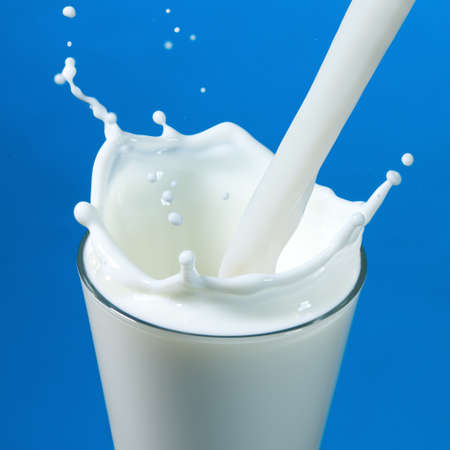 pouring milk in a glass isolated against white background photo