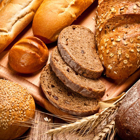 whole grains: assortment of baked bread on wood table