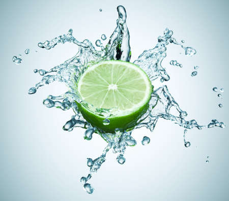 lime in spray of water. lime cucumber with splash on background photo