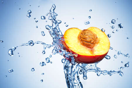 Peach in spray of water. Juicy peach with splash on white background photo