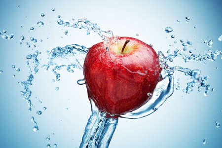Apple in spray of water. Juicy apple with splash on blue background photo