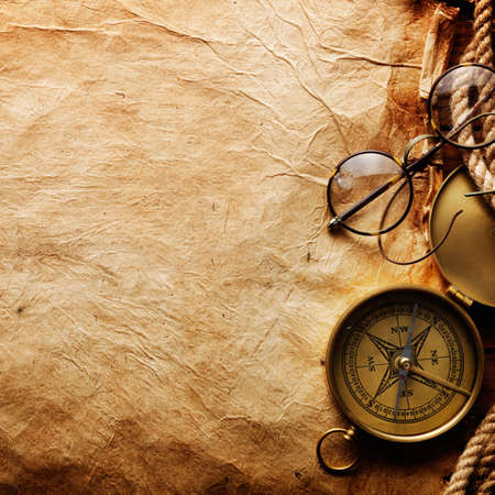 Compass, rope and glasses on old paper photo