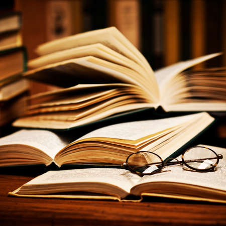 school library: opened book, lying on the bookshelf with a glasses