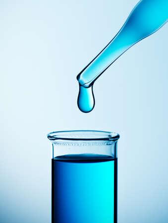 Reageerbuis met pipet over blauwe achtergrond