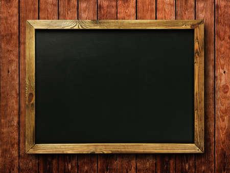 Blank chalkboard in wooden frame on wooden wall photo