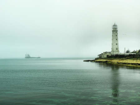 Lighthouse and ship in the fog photo